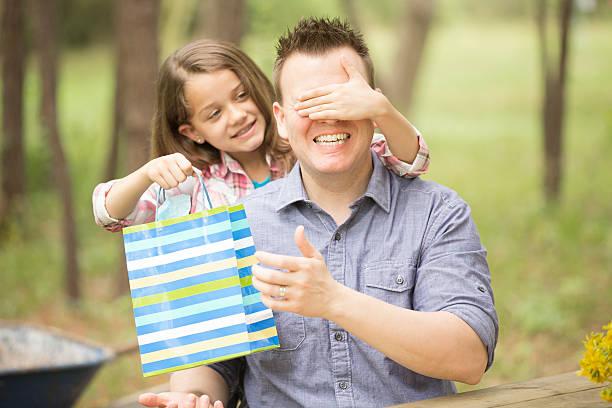 vater überraschungen tochter mit geschenk zum vatertag. outdoor. kinder, eltern. - geburtstagsgeschenk für papa stock-fotos und bilder