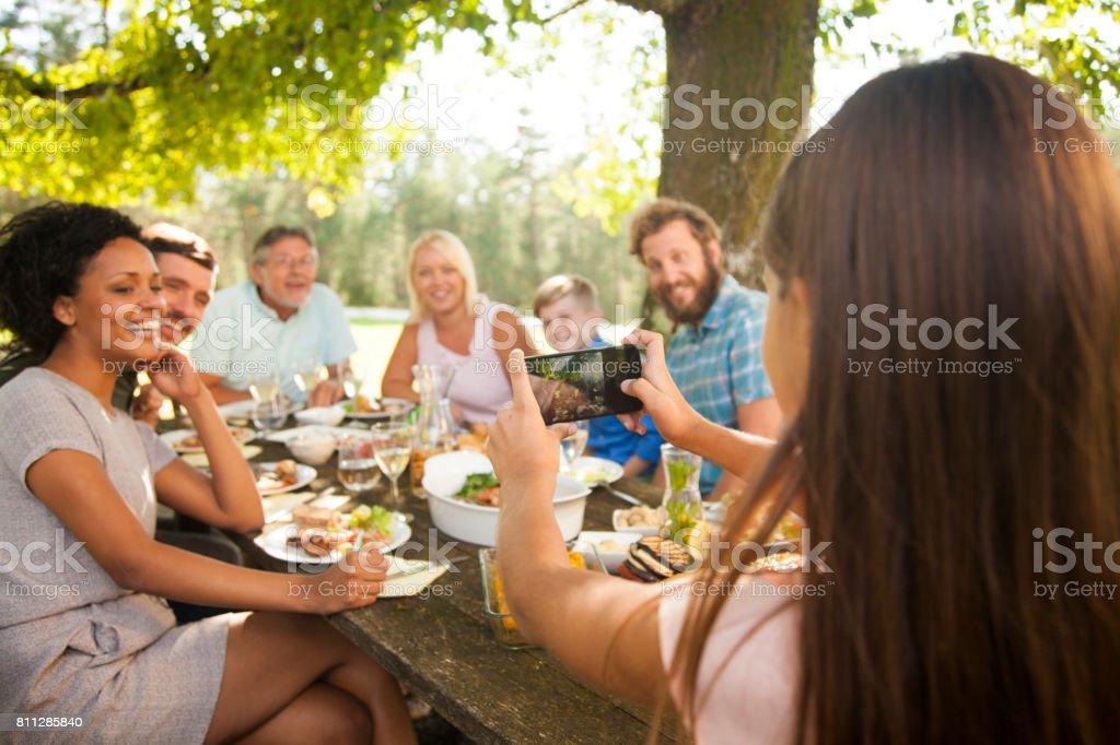 Tochter, die unter einem Gruppenfoto auf ein Familientreffen – Foto