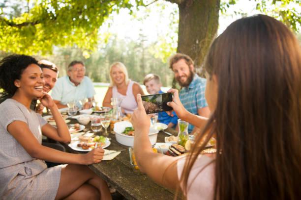 家族の集まりでグループ写真を撮る娘 ストックフォト