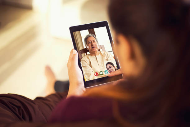 Daughter talking on video call with her father using digital tablet stock photo