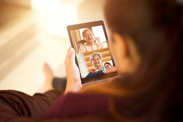 Tochter im Videoanruf mit ihren Eltern mit digitalem Tablet – Foto