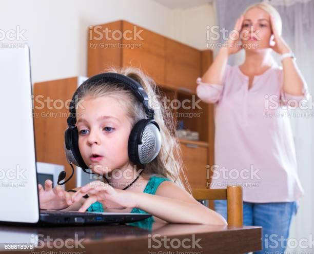 Hija usando ordenador portátil en vez de estudiar - Foto de stock de Adicción libre de derechos