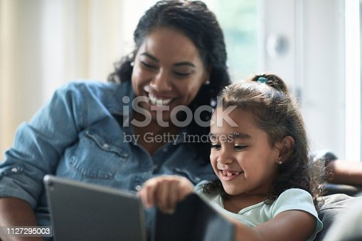 Smiling mother looking at daughter using digital tablet. Woman and girl spending leisure time at home. Family is sitting on sofa.