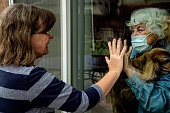 istock A Daughter Visiting Her Quarantined Mother Preventing Contracting Corona Virus Through The Window 1216868219