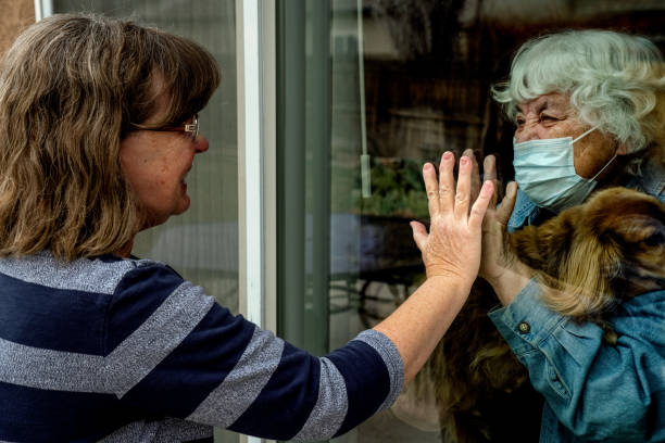 A Daughter Visiting Her Quarantined Mother Preventing Contracting Corona Virus Through The Window A touching moment as a mother visits with her daughter at the window of her home because of having COVID 19 flatten the curve stock pictures, royalty-free photos & images