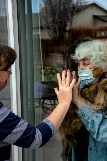 A Daughter Visiting Her Quarantined Mother Preventing Contracting Corona Virus Through The Window stock photo
