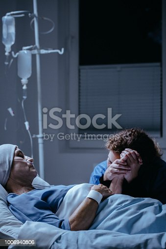928968772 istock photo Daughter visiting sick mother with cancer dying in the hospital 1006940806