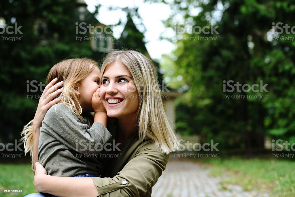 Daughter whispering in mothers ear. stock photo