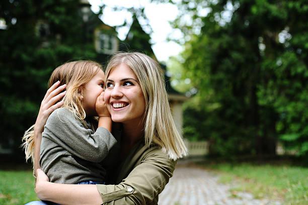 daughter whispering in mothers ear. - der geheime garten stock-fotos und bilder
