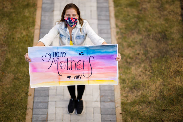 Daughter wishing Happy Mother's Day holding sign stock photo