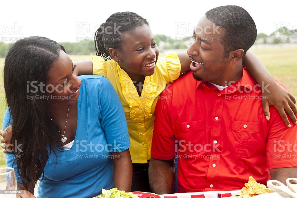 Daughter With Arms Around Her Parents at the Picnic Table royalty-free stock photo