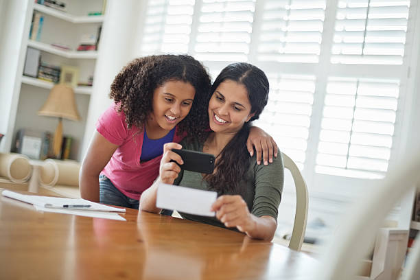 Daughter With Mother Depositing Bank Slip Through Mobile Phone stock photo