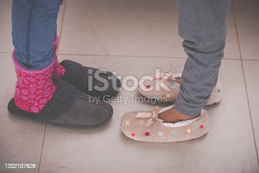 Close up daughter's and mother's feet with warm slippers, staying against each other on a tiled floor. The girl wearing slippers decorated with polka dots and ribbon bow. The woman wearing red warm woolen socks and dark gray slippers. A family at home in the winter season.