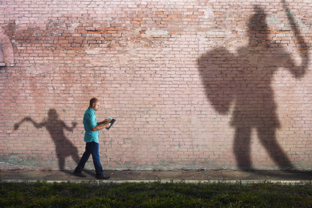 David and Goliath A man reads a Bible while his shadow is David fighting goliath. giant fictional character stock pictures, royalty-free photos & images