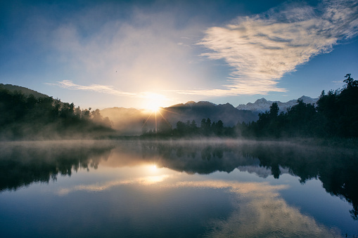 Dawn on New Zealand's South Island, and the Southern Alps are reflected in the mirror-like surface of Lake Matheson.