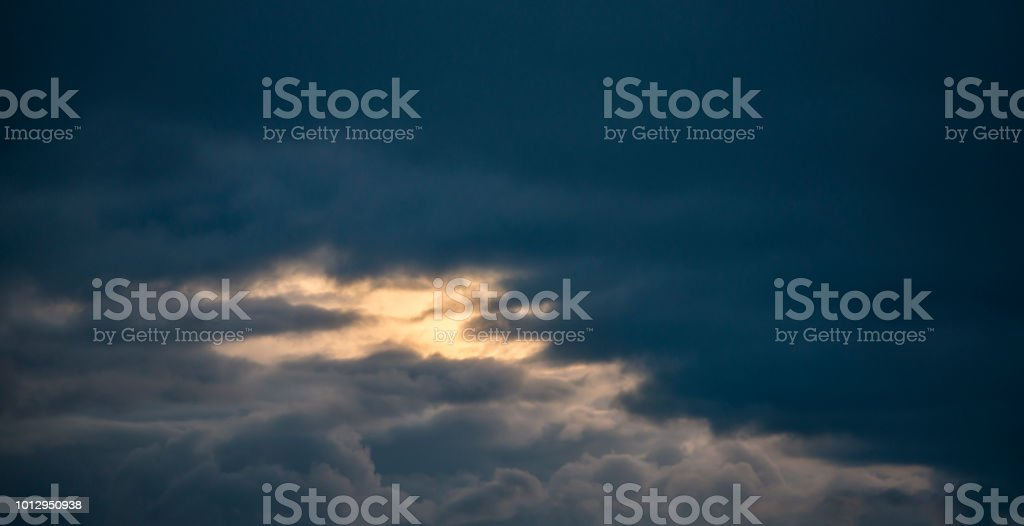Dark clouds at sunrise. Between the clouds is a piece of open sky in...