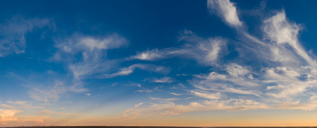 Dawn or sunset, panorama. Drone view of bright clouds sky and sun.
