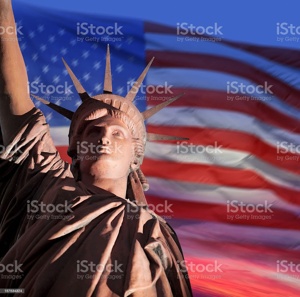 Dawn over Statue of Liberty and American flag stock photo