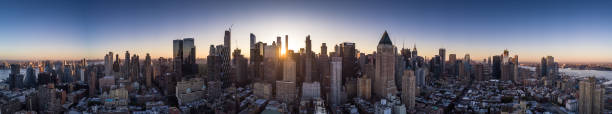 Dawn Panorama of Manhattan - Aerial Shot Panorama taken from a drone flying above Midtown Manhattan at dawn, with the sun about to rise behind the skyscrapers of the financial district. 360 degree view stock pictures, royalty-free photos & images