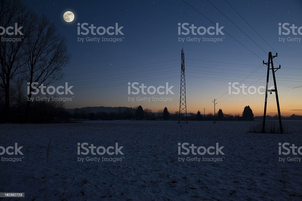 Dawn winter landscape with power pole and moon stock photo