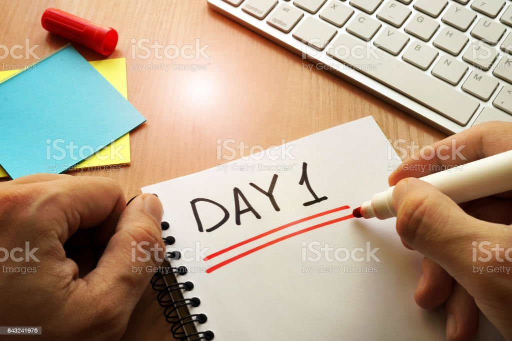Day 1 written in a reminder on table. stock photo
