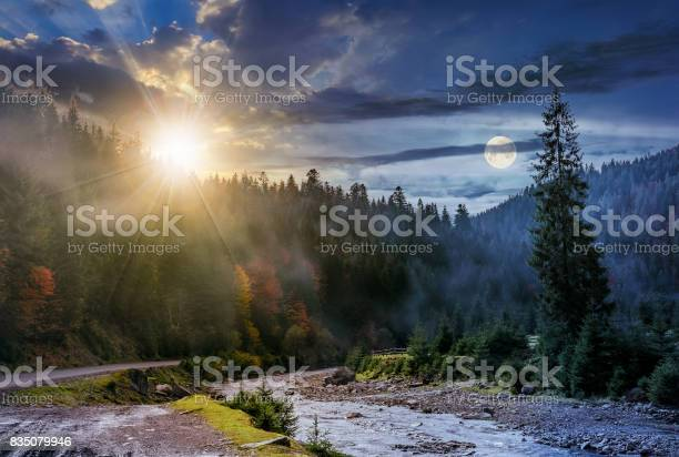 Photo of day and night change over foggy forest and river