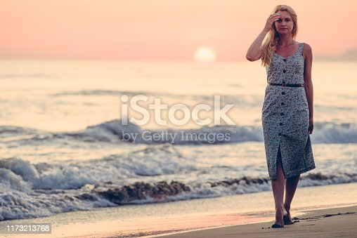 Blonde caucasian woman with an elegant fashionable dress and her wooden bag posing in a portrait session near the sea at sunset