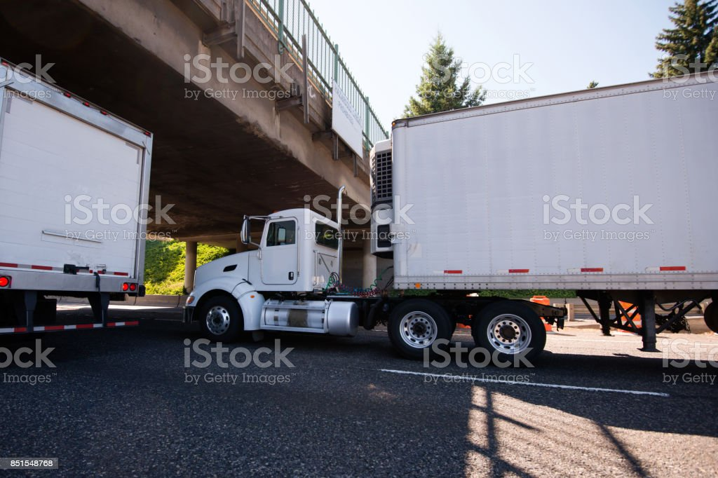 Day cab big rig semi truck going with reefer trailer with refrigeration unit under the bridge on roadside with traffic stock photo