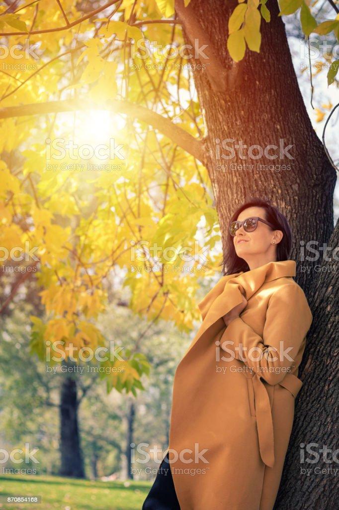 Beautiful woman day dreaming and enjoying in autumn sunshine. Elegant...