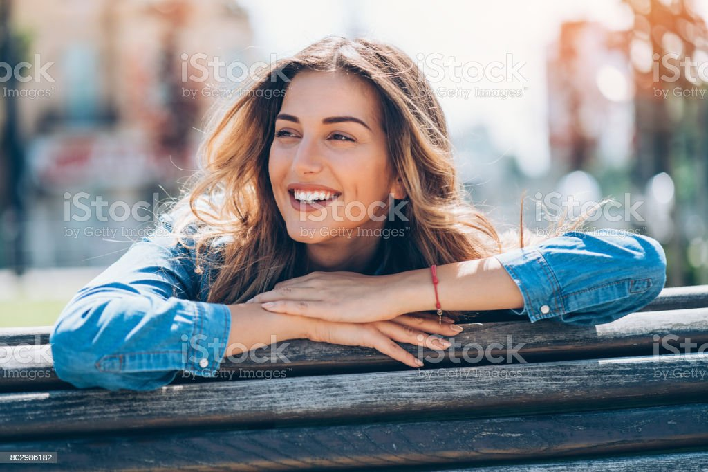 Beautiful young woman sitting and looking away