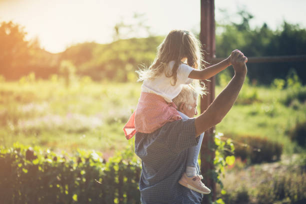 Day for fun Day for fun. Grandfather and granddaughter spending time together in nature. Carrying on shoulders. Copy space. granddaughter stock pictures, royalty-free photos & images