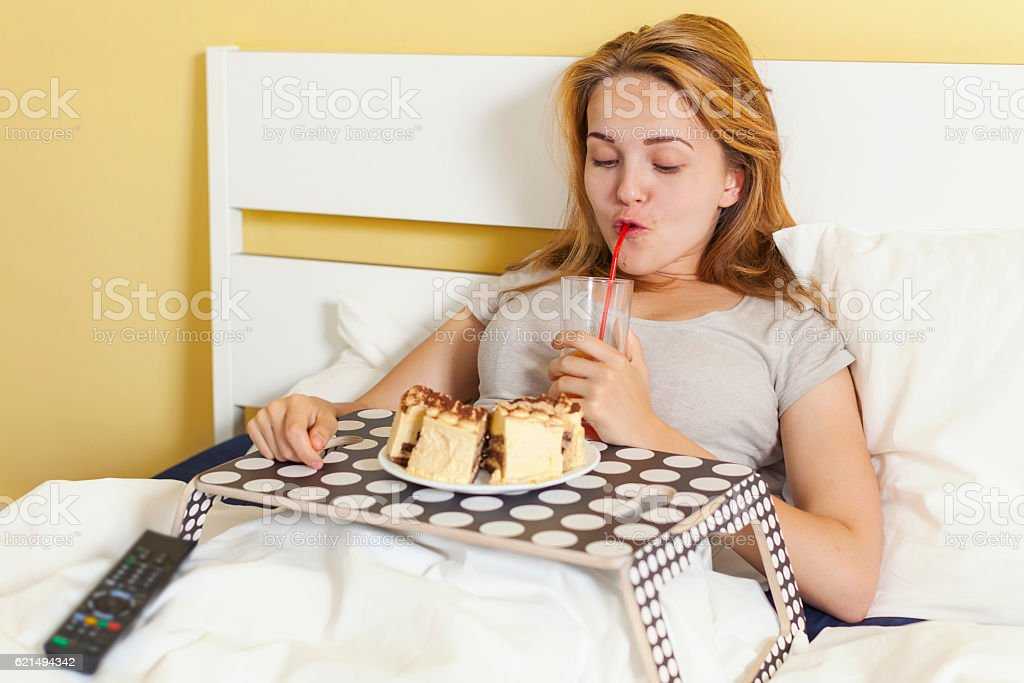 Day gluttony, teen girl eating a cake and drinks soda photo libre de droits