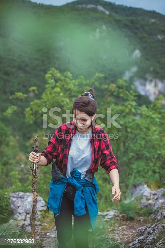 A view of a young adventurer, enjoying her weekend in nature, climbing the high mountain nearby. She's all about the journey, says the smile on her face.