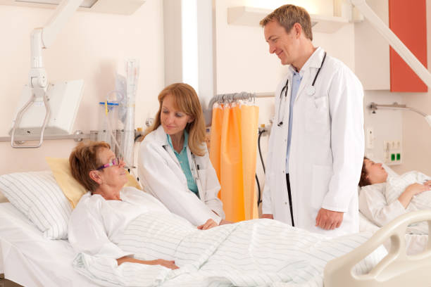 Day in the Life of a Patient, doctors and patient in hospital room stock photo