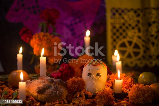 Mexican traditional altar for day of the day celebration with sugar skull, bread, yellow cempasuchil flowers and candle light