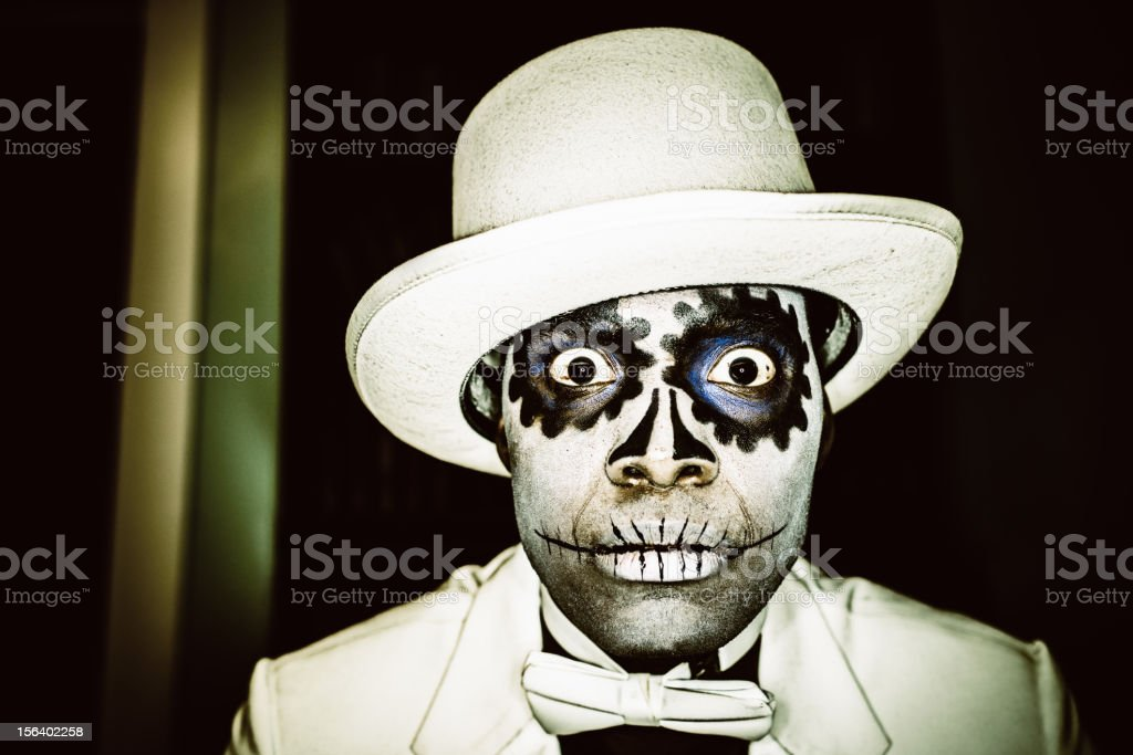 Day of the Dead Man Bizarre Portrait Man with typical Mexican-style Day of the Dead (Dia de los Muertos), sugar skull make-up, dressed in white suit and hat. Dark, Surreal Portrait. Adult Stock Photo