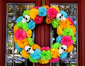 Day of the Dead wreath on door with tree and neighborhood reflected in beveled glass window
