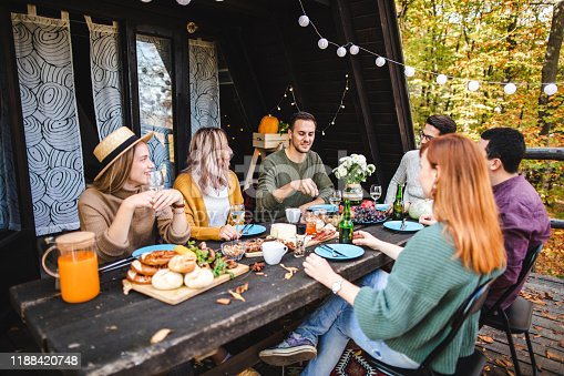 Six friends talking and smiling during brunch at cabin outside of the city on autumn day