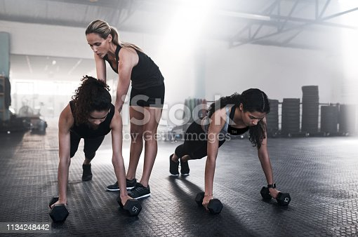 Shot of young women working out with dumbbells and a trainer at the gym