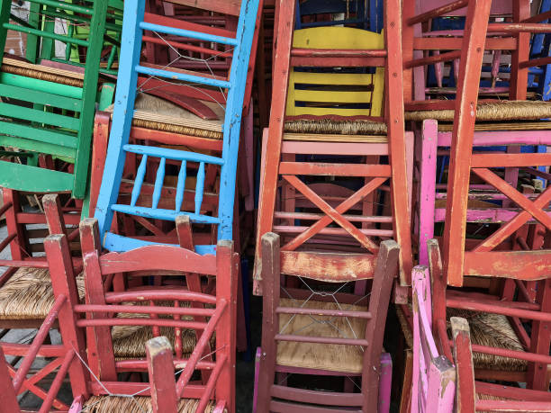 Day sunny view of tavern style chairs in random disarray and bright colours in Greece. stock photo