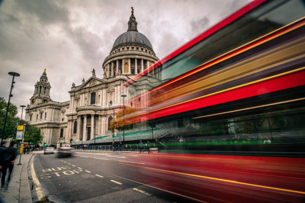 Day time view of Saint Paul's Cathedral in London city - creative stock image Long exposure, cloudy weather day time view of Saint Paul's Cathedral in London city with motion blur traffic, including:(double decker bus, cars, tourists and commuters). Shot on Canon EOS R full frame system with extra wide lens for premium quality. central london stock pictures, royalty-free photos & images