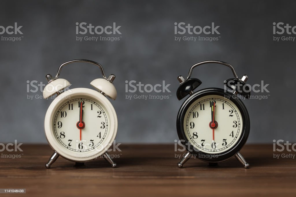 Black and white vintage / retro alarm clock on wooden table on bark...
