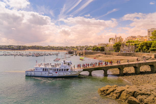 Day tripping tourists line up to start boarding ferry on the return trip to Saint Malo from Dinard pier. stock photo
