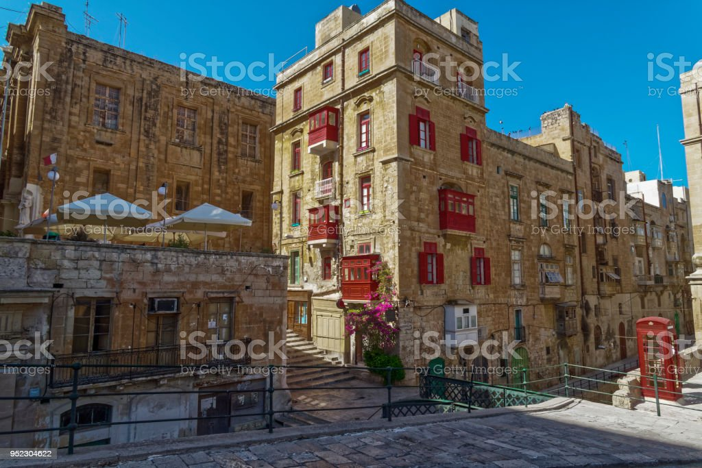 Day view of Maltese limestone buildings with British phone booth in the streets of the capital of Malta. stock photo
