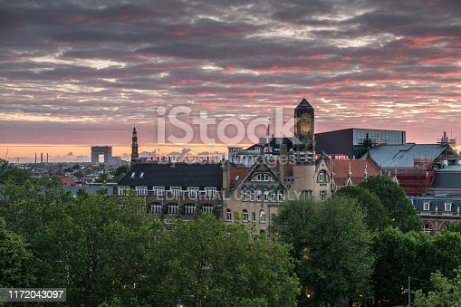 Amsterdam, the Netherlands - July 2, 2019: Yellow and red lights cut by dark clouds in sky over towers and roofs. Leidseplein up front. Westerkerk spire. Modern Pontsteiger high rise.