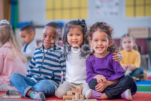 A multi-ethnic group of daycare children sit close together on the floor, with their legs crossed and their arms around one another, as they pose for a portrait.  They are smiling and enjoying their time together.