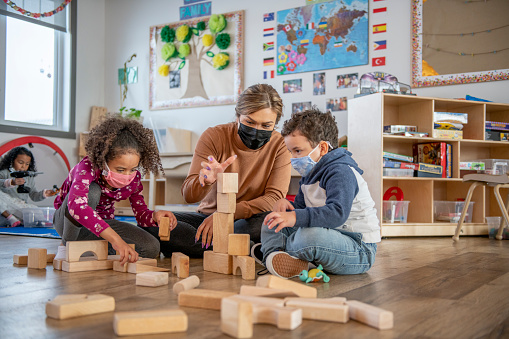 A teacher helps daycare kids build a structure with wooden blocks on the floor.