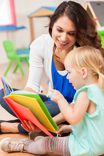 Daycare teacher reading to cute toddler girl stock photo