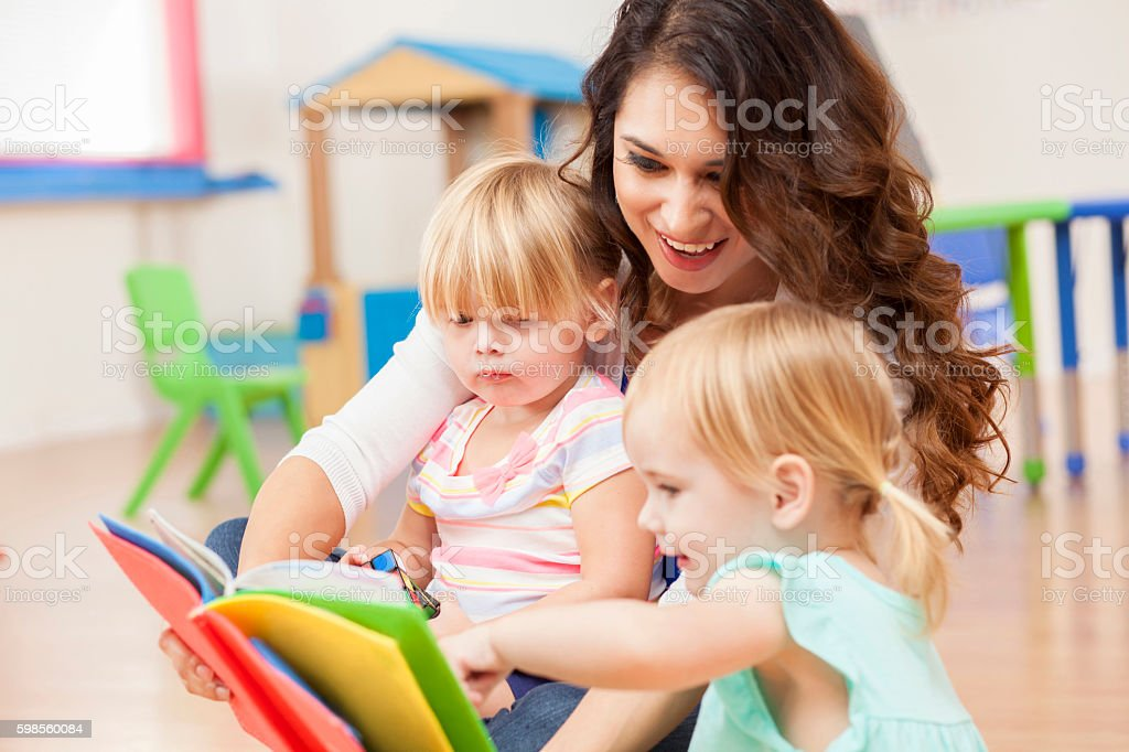 Daycare teacher reading to cute toddler girls stock photo