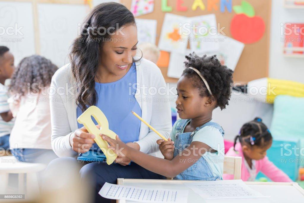 Happy preschool teacher holds the letter \'B\' while teaching a little...